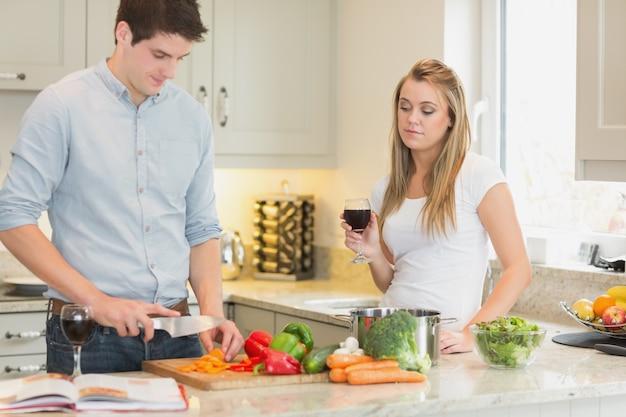 Homem cozinhar com mulher bebendo vinho tinto Foto Premium
