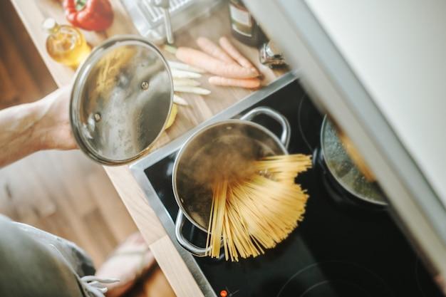 Homem cozinhar macarrão na cozinha