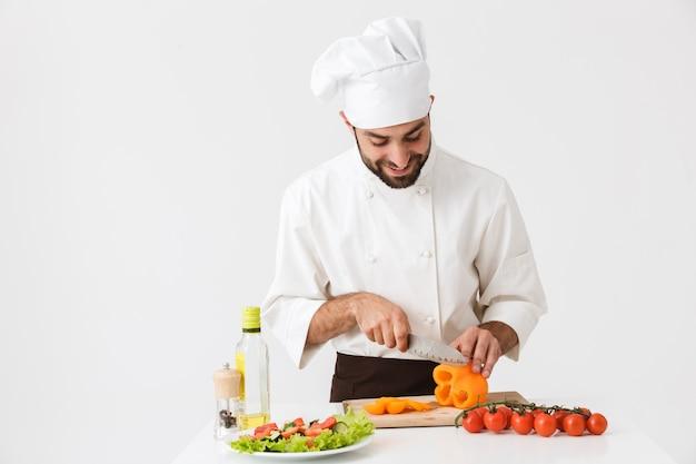 Homem cozinheiro caucasiano de uniforme sorrindo e cortando salada de legumes na placa de madeira isolada na parede branca