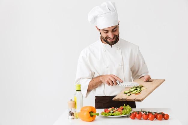 Homem cozinheiro positivo de uniforme sorrindo e cortando salada de legumes na placa de madeira isolada sobre a parede branca
