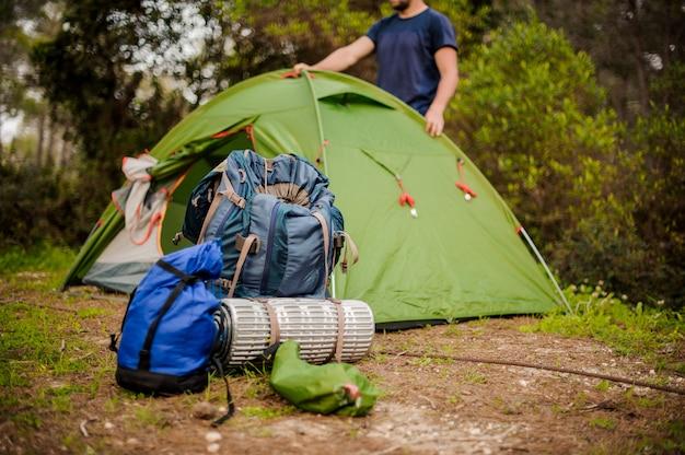 Homem cria uma tenda verde perto do equipamento de caminhadas