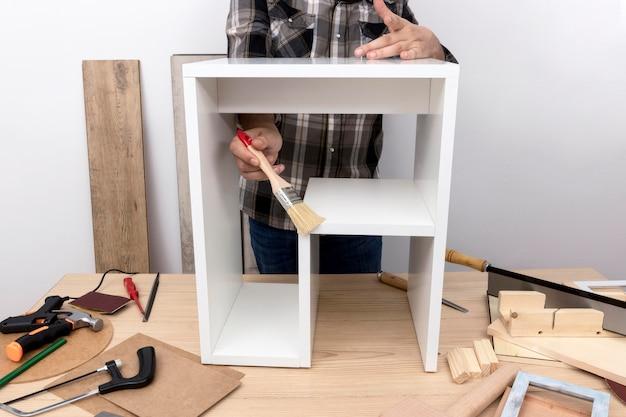 Homem criando um armário da vista frontal de madeira