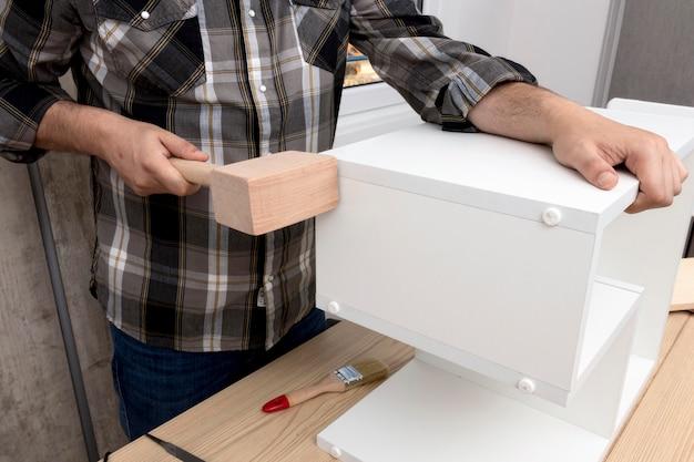 Homem criando um armário de madeira