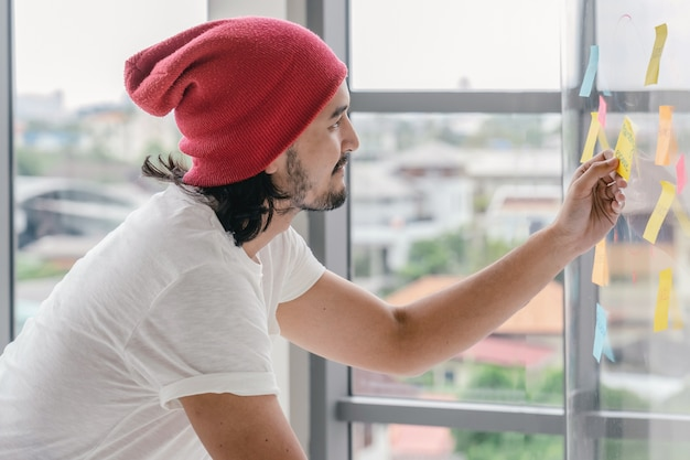 Homem criativo asiático escrevendo e apontando o postit na placa de millor ao apresentar o