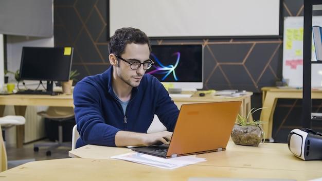 Homem criativo de óculos usando laptop no local de trabalho em um escritório moderno e luminoso