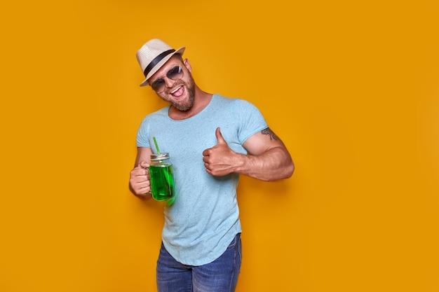 Homem criativo em óculos de sol e roupas de verão, chapéu elegante em pé relaxado e bebendo de creati ...