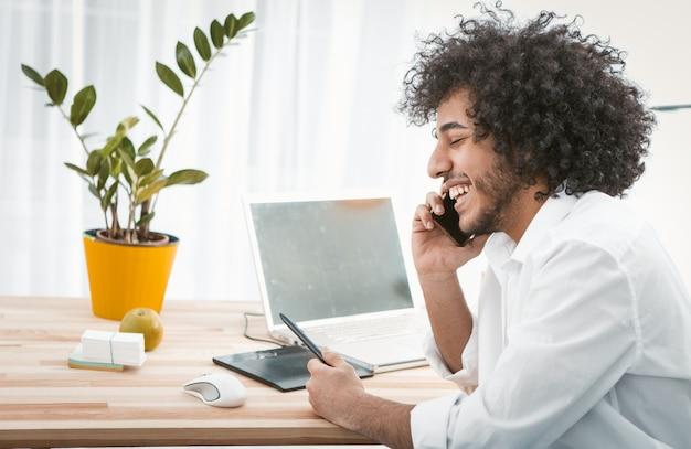 Homem criativo se comunica pelo telefone móvel, sorrindo enquanto está sentado em casa no local de trabalho. conceito freelance. trabalhe em casa conceito. vista lateral. copie o espaço no lado esquerdo. imagem enfraquecida