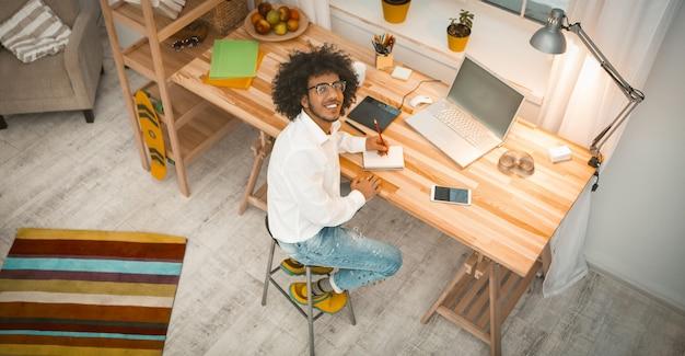 Homem criativo trabalha sentado na mesa de madeira grande em um interior elegante em casa enquanto olha para a câmera. vista de alto ângulo. imagem enfraquecida