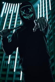 Homem criminoso anônimo com taco de beisebol em um capuz preto e máscara de néon