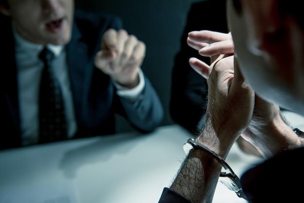 Homem criminoso com algemas sendo entrevistado na sala de interrogatório