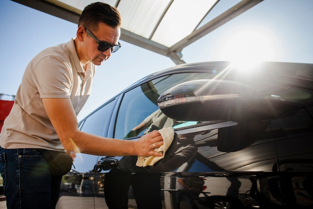 Homem cuidadosamente polir um carro preto