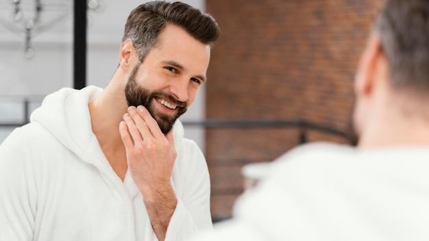 Homem cuidando bem do rosto em casa