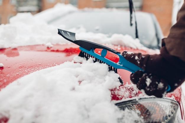 Homem cuidando de automóvel remover gelo com escova ao ar livre
