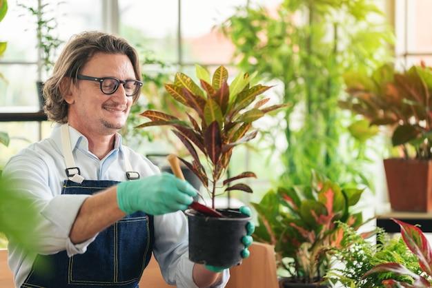 Homem cuidando de seus vasos de plantas em casa, jardinagem, plantando em casa