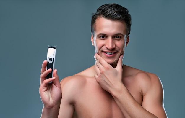 Homem cuidando de sua higiene em uma sala cinza