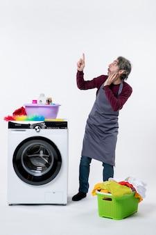 Homem curioso de governanta de vista frontal em pé perto do cesto de roupa suja da máquina de lavar em fundo branco