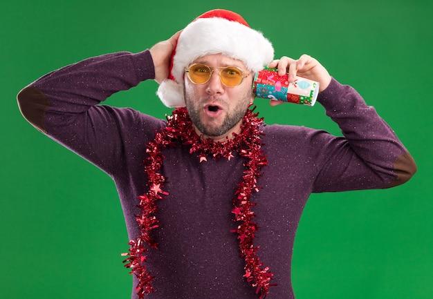 Homem curioso de meia-idade usando chapéu de papai noel e guirlanda de ouropel no pescoço, óculos segurando um copo de natal de plástico próximo à orelha, ouvindo segredos