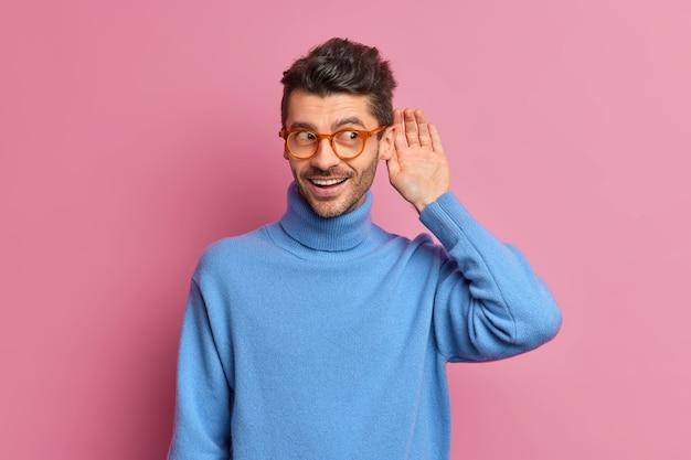 Homem curioso e alegre com a barba por fazer mantém a mão perto do ouvido tentando ouvir uma conversa particular ouve fofocas