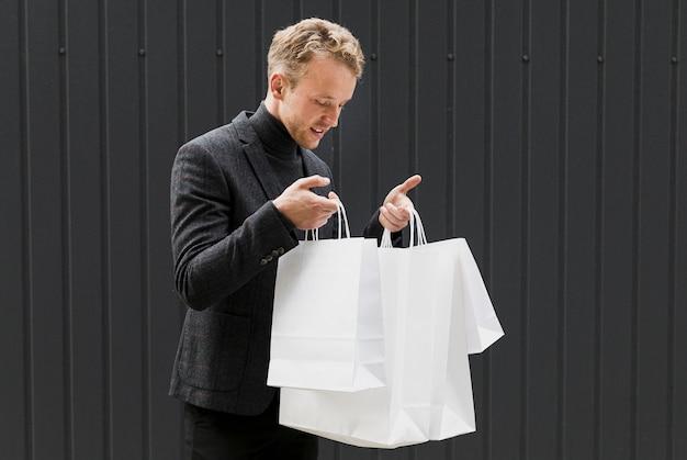 Homem curioso em preto olhando em sacolas de compras