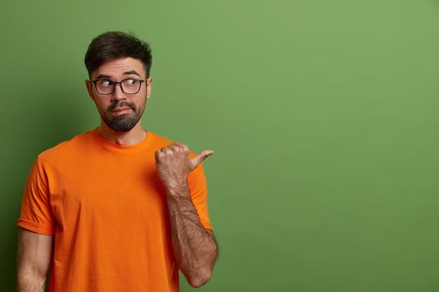 Homem curioso olha com desconfiança e interesse à parte, aponta para o lado no espaço em branco, mostra anúncio de produto ou banner da empresa, faz gestos contra parede verde, usa óculos, camiseta.