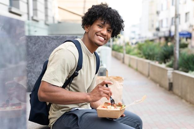 Homem curtindo comida para viagem ao ar livre