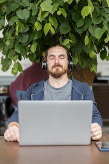Homem curtindo música em um terraço com laptop