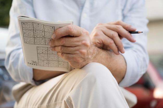 Homem curtindo um jogo de sudoku no papel