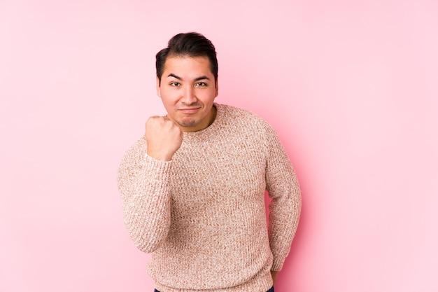 Homem curvilíneo jovem posando em um espaço rosa isolado mostrando o punho para a câmera, expressão facial agressiva.