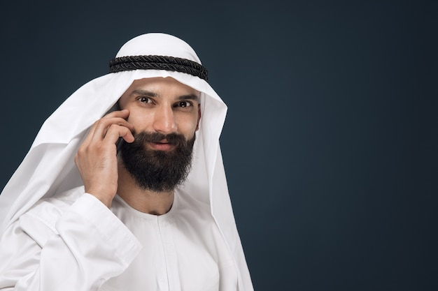 Homem da arábia saudita em estúdio azul escuro