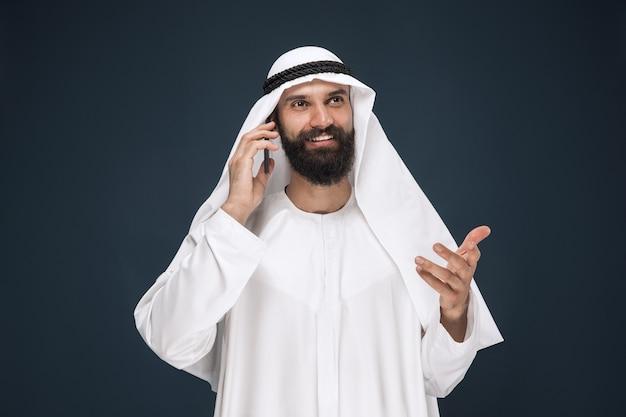 Homem da arábia saudita em fundo azul escuro do estúdio