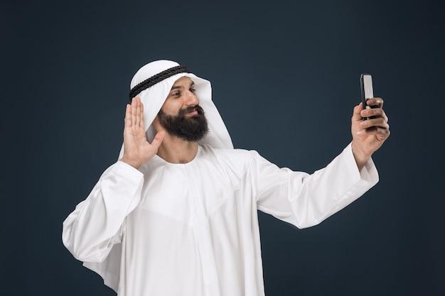 Homem da arábia saudita em parede azul escura