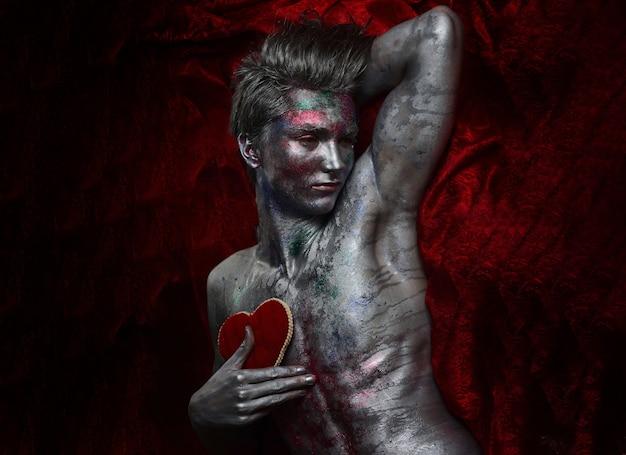 Homem da arte com torso nu segura coração macio vermelho no peito com tinta prateada cintilante e brilhos coloridos