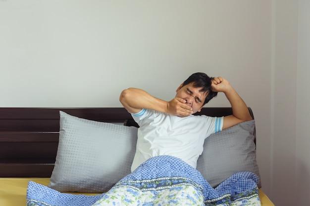 Homem da ásia, estendendo-se na cama depois de acordar
