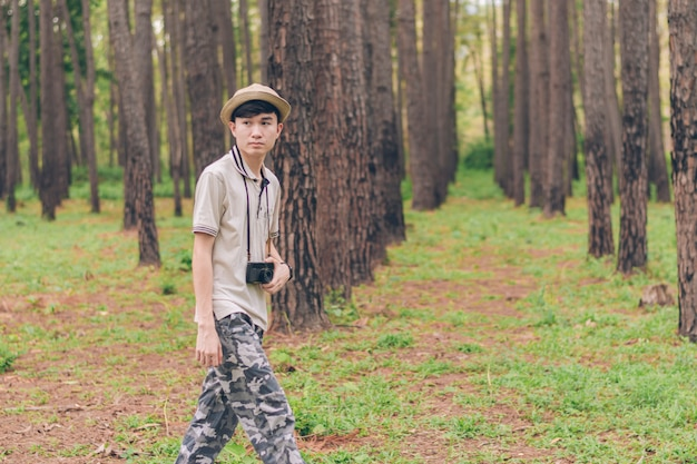 Homem da ásia usa camisa, chapéu e calças de camuflagem estão andando e tirando fotos na floresta