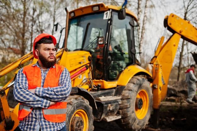Homem da barba trabalhador terno trabalhador da construção civil no capacete de segurança laranja contra trator.