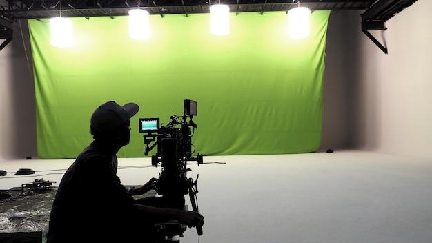 Homem da câmera, ferramentas, piso branco e estúdio com tela verde grande.