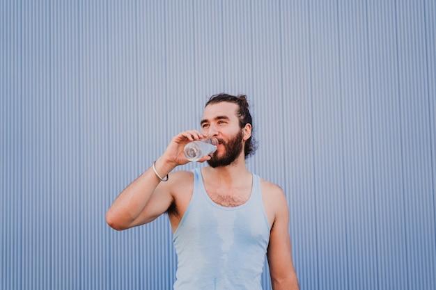 Homem da cidade praticando esporte de ioga e água potável