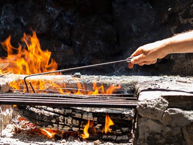 Homem da colheita que verifica cinzas na fogueira