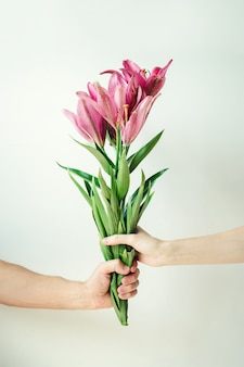 Homem dá flores para mulher. mão masculina e feminina, segurando o buquê em fundo branco