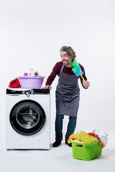 Homem da governanta exultante de vista frontal segurando o espanador em pé perto do cesto de roupa suja da máquina de lavar roupa no fundo branco