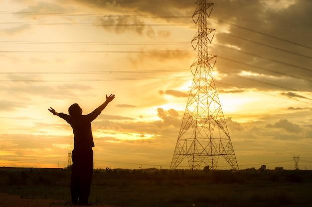 Homem da liberdade com as mãos levantadas no por do sol crepuscular para o deus rezando.