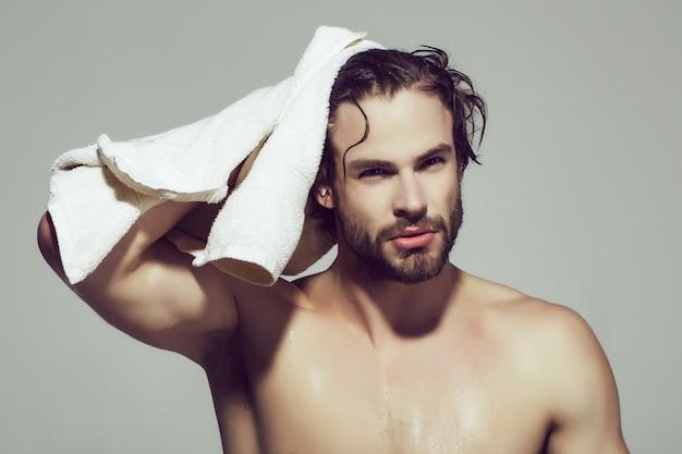 Homem da manhã com corpo musculoso molhado segura toalha no banho ou duche após a lavagem, higiene e cuidados com a pele, saúde e despertar.