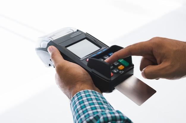 Homem da mão com a máquina de cartão de crédito.