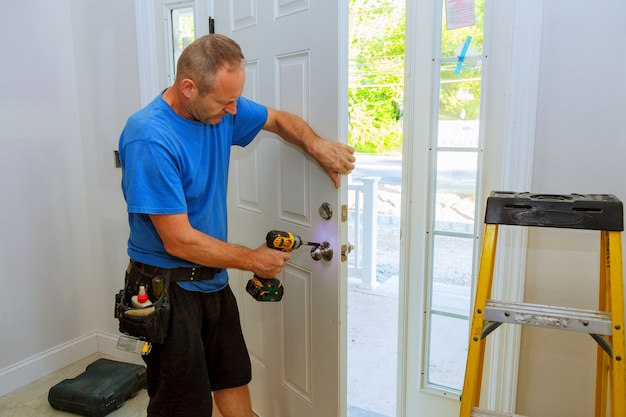 Homem da mão com chave de fenda instala maçaneta da porta