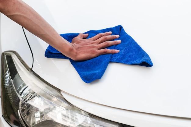 Homem da mão com pano de microfibra, polimento de carro