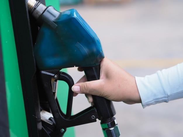 Homem da mão do close up que bombeia o combustível da gasolina no carro no posto de gasolina.