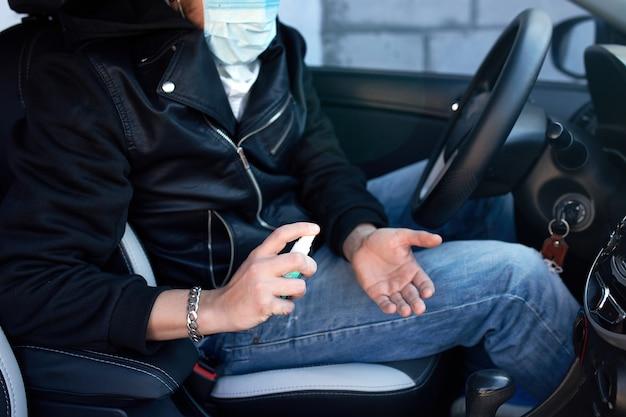 Homem da máscara de proteção sentado no carro, pulverizando as mãos spray desinfetante antibacteriano para prevenção de doença de coronavírus