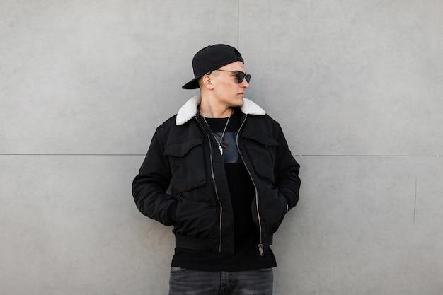 Homem da moda com roupas elegantes perto de uma parede cinza