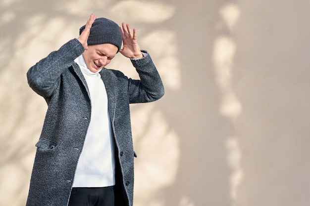 Homem da moda jovem atraente hippie com os olhos fechados, vestindo um casaco cinza, blusa branca e calça jeans preta, segurando as mãos perto da cabeça e gritando.