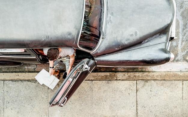 Homem da moda jovem hippie com tatuagem assistindo celular inteligente em carro antigo durante viagem em cuba